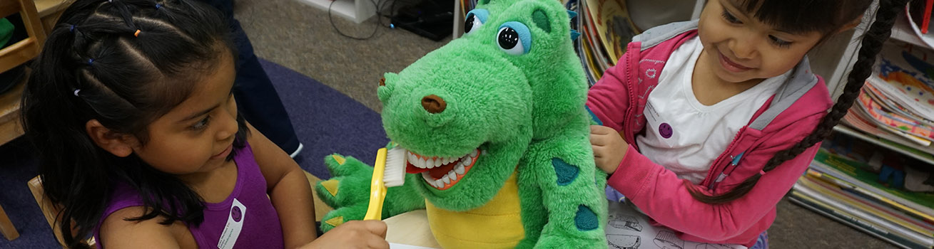 Two young children sitting with a stuffed dinosaur and brushing its teeth