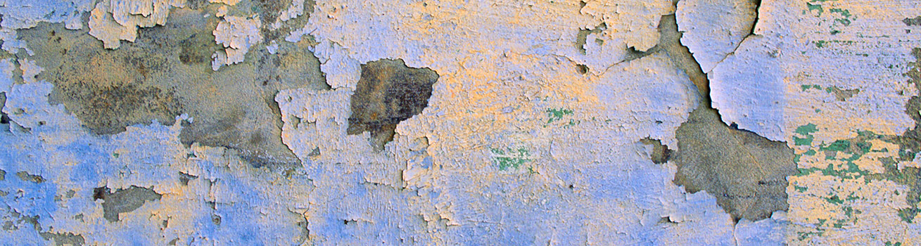 A wall with faded, peeling paint
