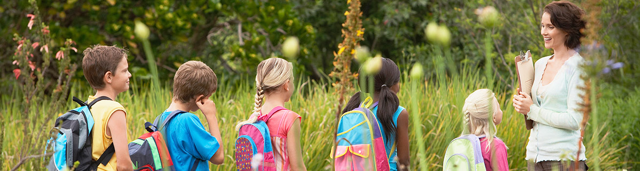 A group of five children with backpacks in a field of tall grass and led by a teacher